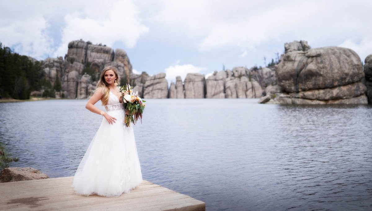 Bride on a dock overlooking a lake