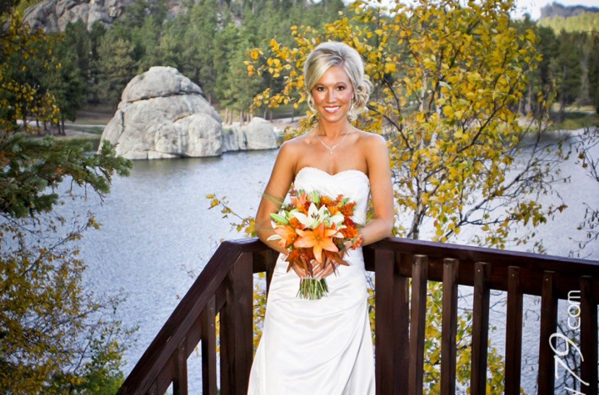Bride on a deck with a lake behind her