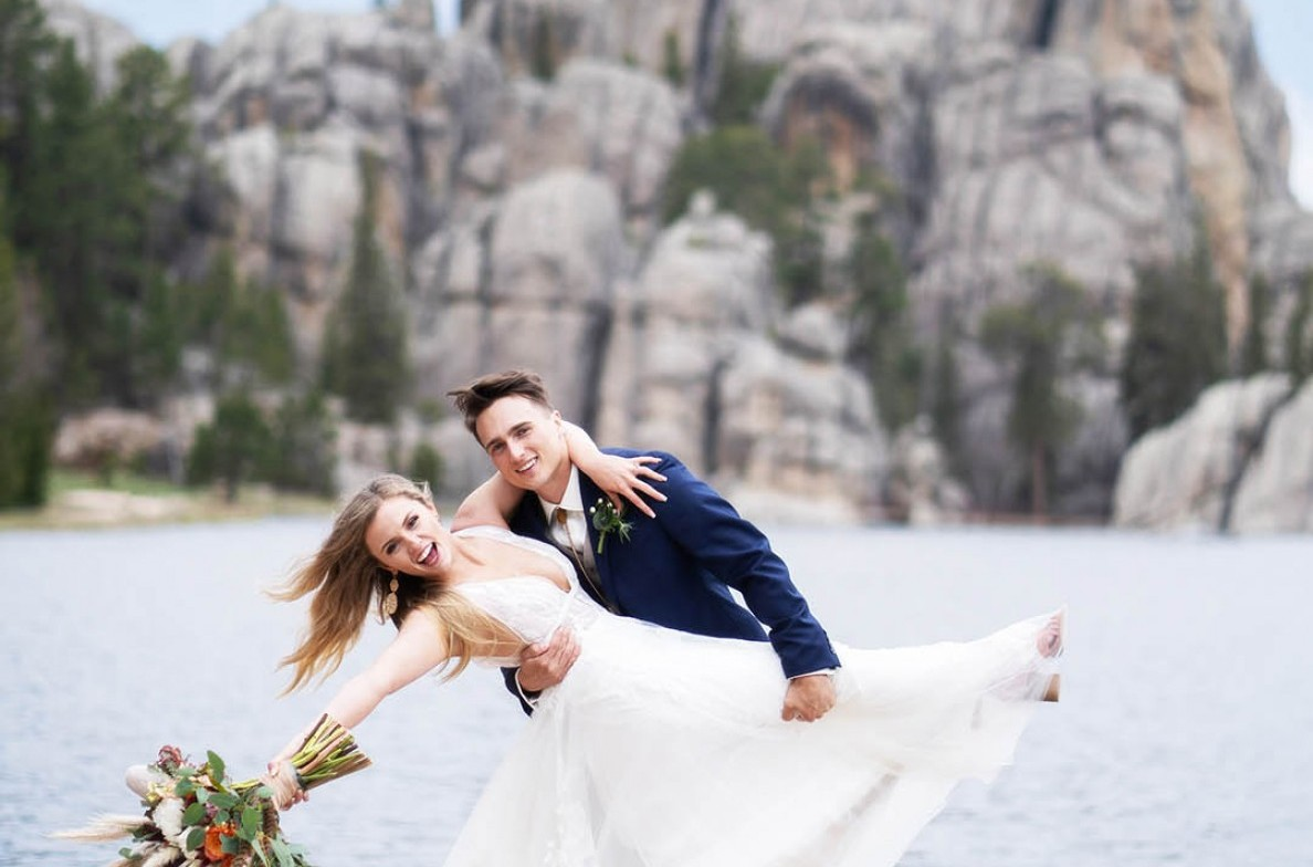 Groom dipping his Bride in front of a lake and rocks